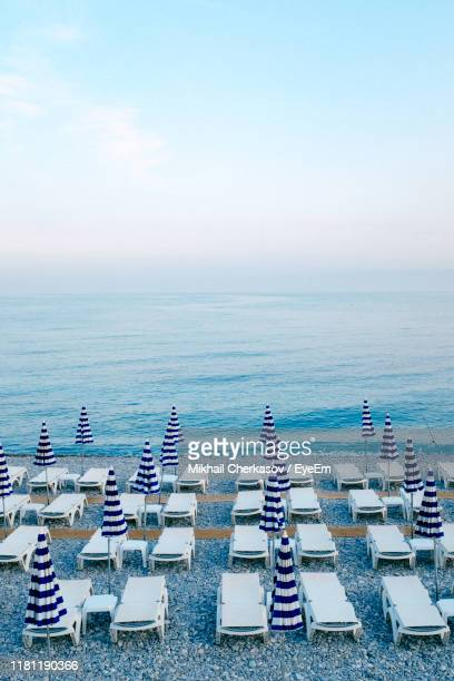 high angle view of deck chairs with parasols at beach against sky - french riviera stock pictures, royalty-free photos & images