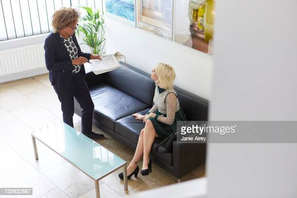 High angle view of designer and woman sitting on sofa in office lobby