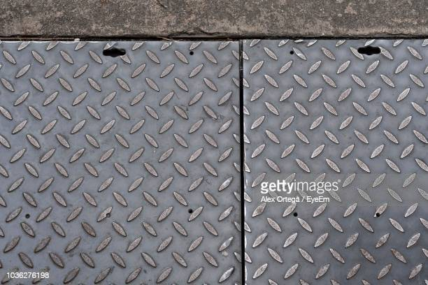 High Angle View Of Diamond Plates On Footpath