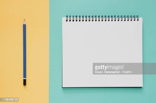 high angle view of diary with pencil on colored background - spiralblock stock-fotos und bilder