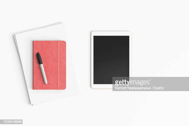 High Angle View Of Digital Tablet By Diary Over White Background