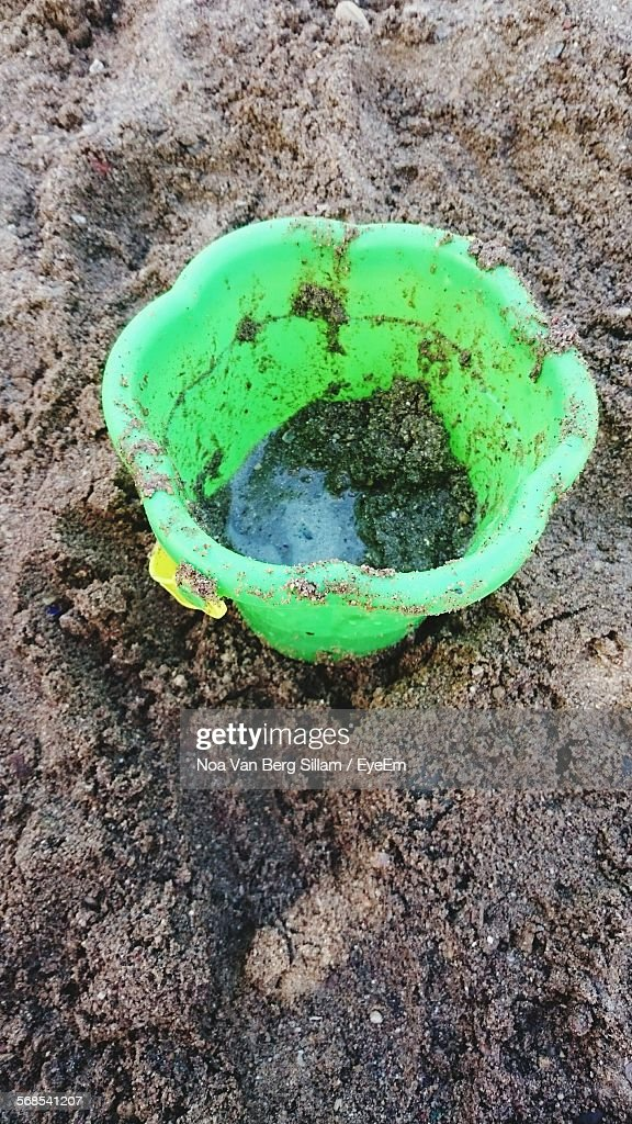 High Angle View Of Dirty Bucket At Beach : Stock Photo