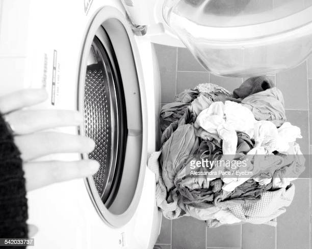high angle view of dirty clothes by washing machine - launderette stock pictures, royalty-free photos & images