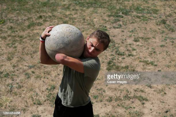 High angle view of disabled male athlete carrying atlas stone while standing on field during sunny day