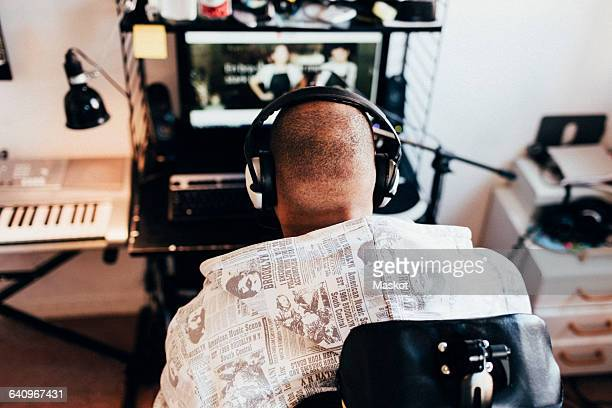 high angle view of disabled musician listening to music at recording studio - assistive technology stock photos and pictures