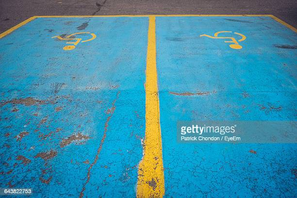 high angle view of disabled sign at parking lot - disabled sign stock photos and pictures