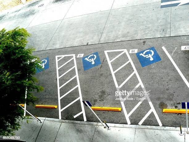 high angle view of disabled signs and markings at parking lot - disabled sign stock photos and pictures