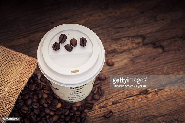 High Angle View Of Disposable Cup And Coffee Beans On Wooden Table
