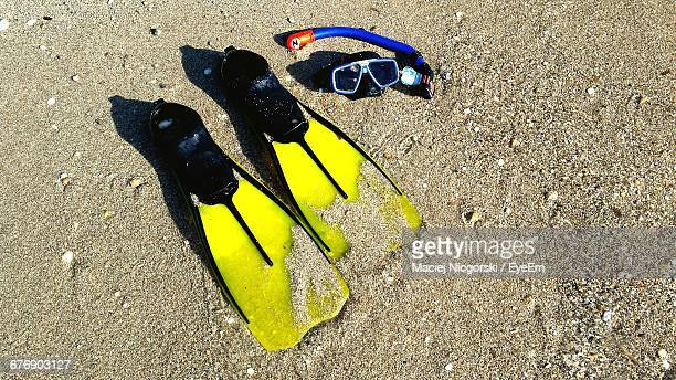 High Angle View Of Diving Flippers And Scuba Mask At Beach