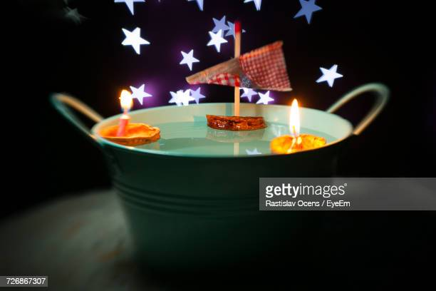 High Angle View Of Diyas And Toy Boat Floating On Water In Container