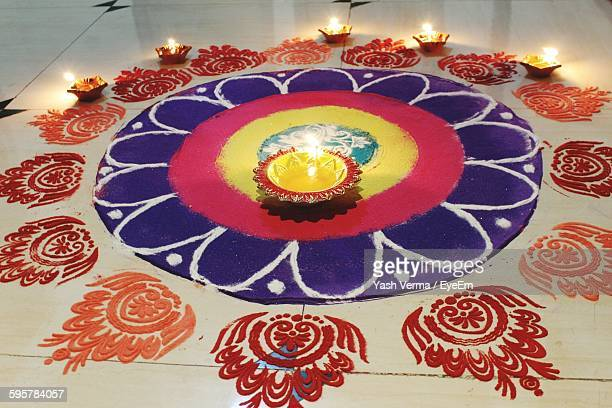 high angle view of diyas on colorful rangoli - diya oil lamp stock pictures, royalty-free photos & images
