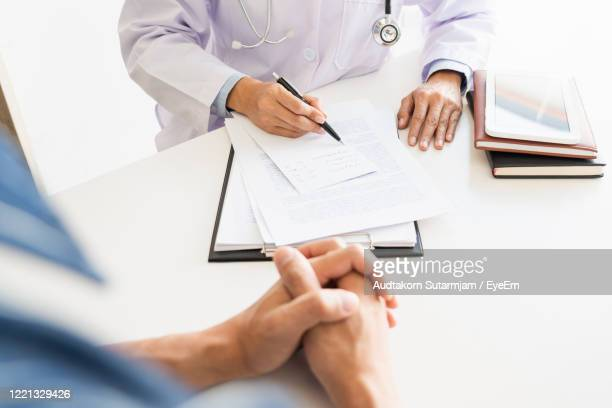 high angle view of doctor and patient on table - mittlerer teil stock-fotos und bilder