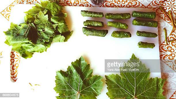 high angle view of dolmades and vegetables on cutting board - dolmades stock pictures, royalty-free photos & images