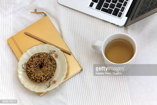high angle view of donut and drink on table - food journal stock-fotos und bilder