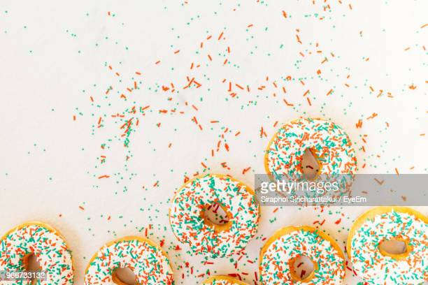 high angle view of donuts on white background - sugar sprinkles stock pictures, royalty-free photos & images