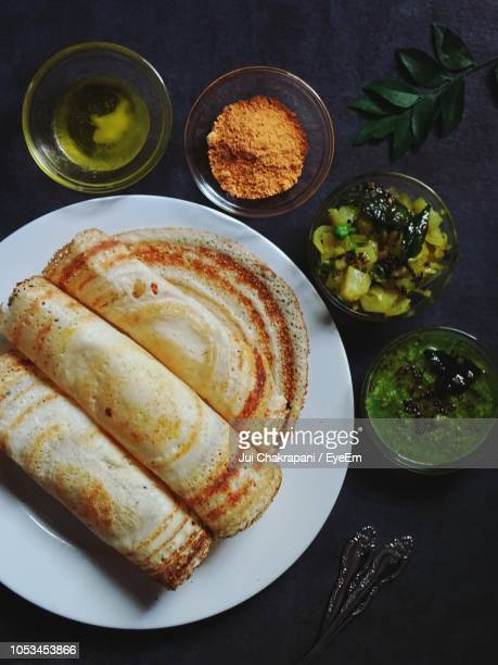 high angle view of dosa in plate on table - dosa stock photos and pictures