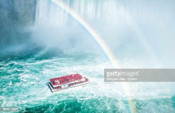 high angle view of double rainbow over cruise ship in sea - niagara falls photos stock photos and pictures