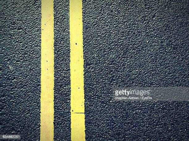 high angle view of double yellow line on road - dividing line road marking stock pictures, royalty-free photos & images
