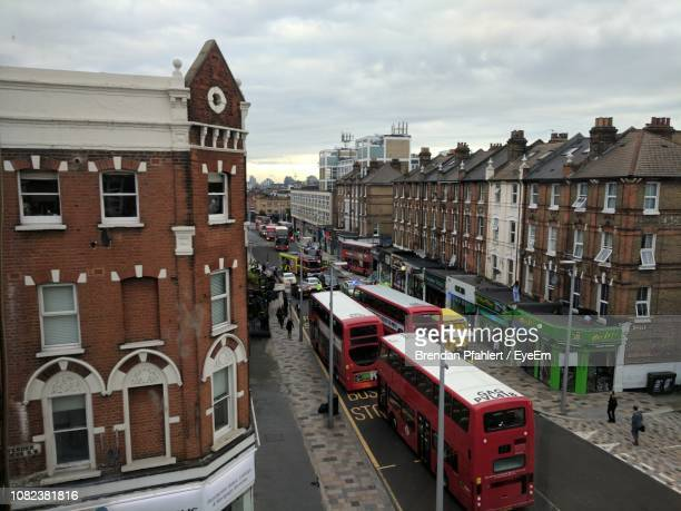 high angle view of double-decker buses on street amidst buildings in city - wandsworth stock pictures, royalty-free photos & images