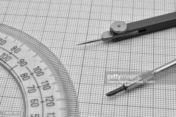 high angle view of drawing compass by protractor on paper - drawing compass stock pictures, royalty-free photos & images