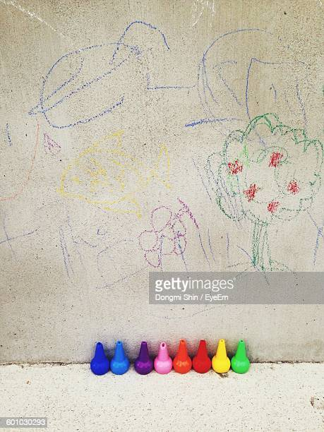High Angle View Of Drawing On Wall With Colorful Crayons