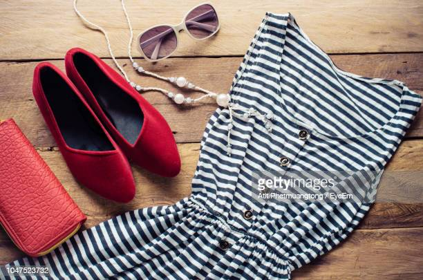high angle view of dress with necklace and shoes on table - striped dress stock photos and pictures
