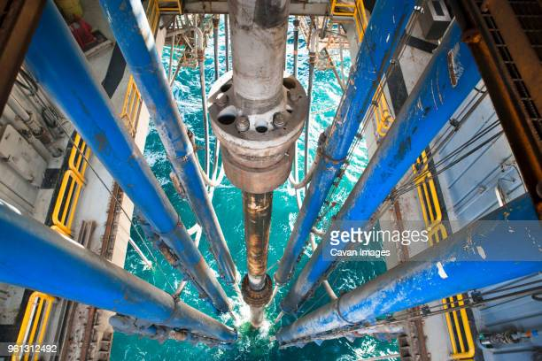 high angle view of drilling riser and pipes in sea at oil rig - oil rig stock pictures, royalty-free photos & images