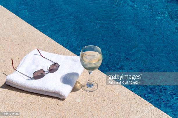 High Angle View Of Drink By Towel And Eyeglasses At Poolside