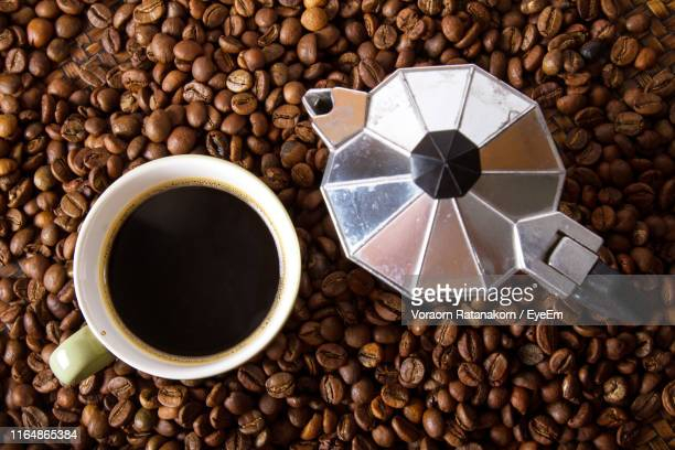 high angle view of drink with coffee maker and roasted beans at table - coffee drink stock pictures, royalty-free photos & images