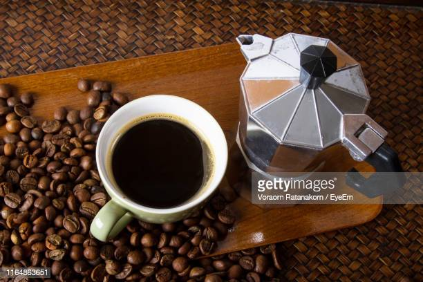 high angle view of drink with coffee maker and roasted beans on serving board at table - coffee drink stock pictures, royalty-free photos & images