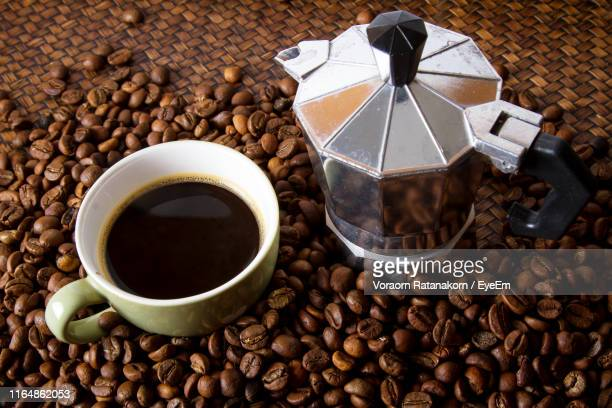 high angle view of drink with coffee maker and roasted beans on table - coffee drink stock pictures, royalty-free photos & images