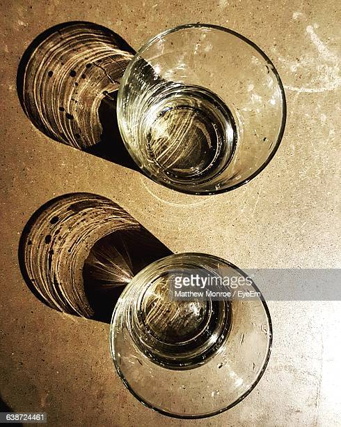 High Angle View Of Drinking Glass With Reflection On Table