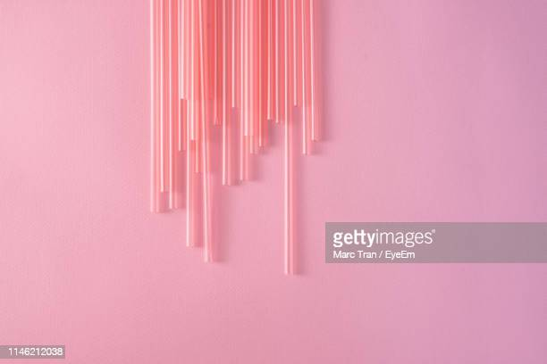 High Angle View Of Drinking Straws On Pink Background