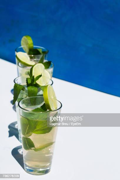 high angle view of drinks at swimming pool - mojito stock photos and pictures