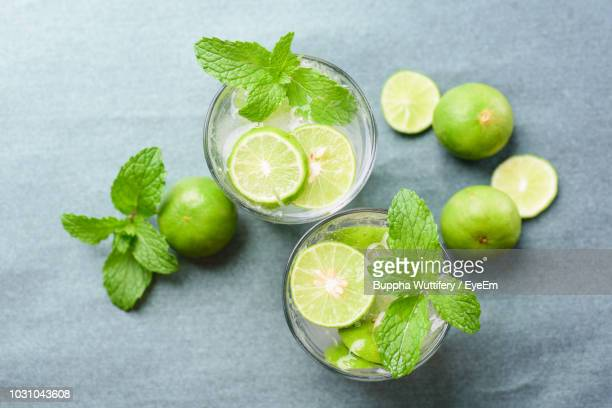 high angle view of drinks with limes and mint leaves on table - ミント ストックフォトと画像