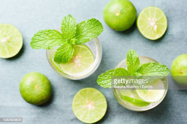 high angle view of drinks with limes on table - ライム ストックフォトと画像