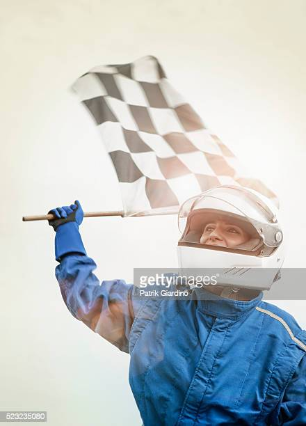 High angle view of driver standing on racecar with checkered flag
