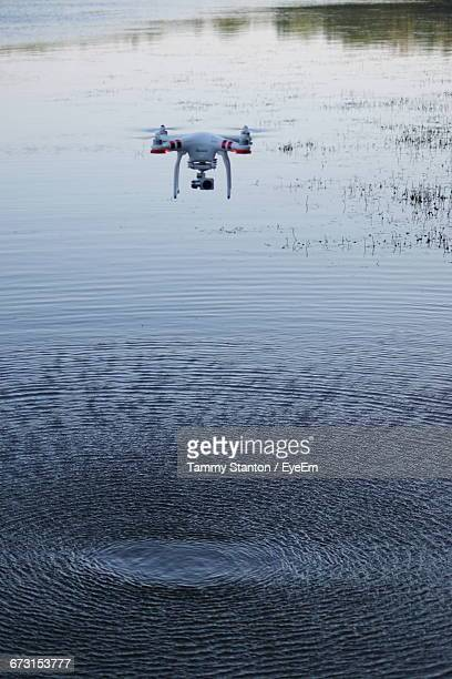 high angle view of drone flying over lake - オクトコプター ストックフォトと画像