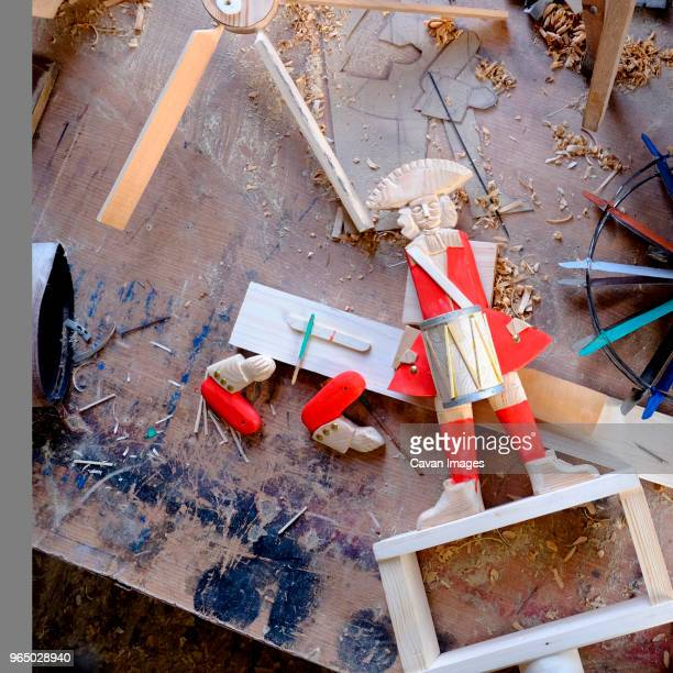 High angle view of drummer figurine on messy wooden table