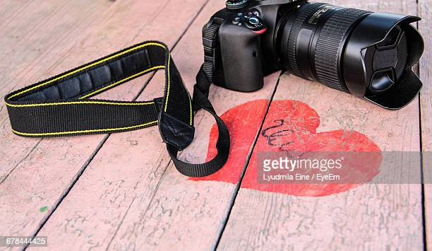 High Angle View Of Dslr Camera By Red Heart Shape On Table