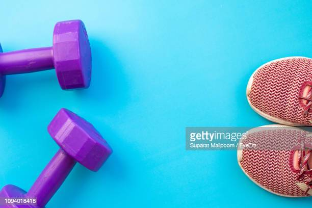 high angle view of dumbbells and shoes against blue background - dumbbell stock pictures, royalty-free photos & images