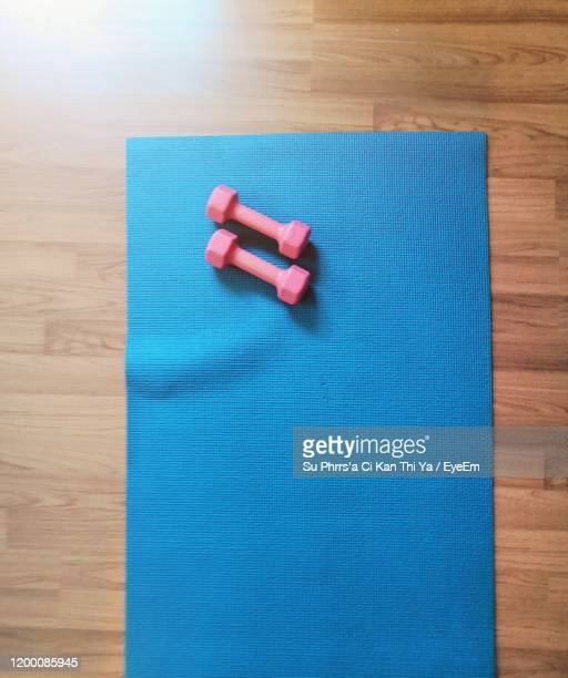 high angle view of dumbbells on hardwood floor - mat stock pictures, royalty-free photos & images