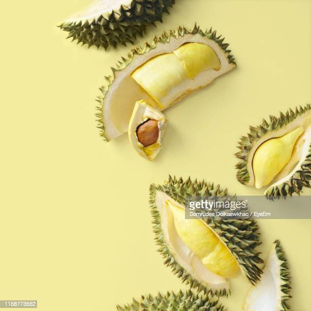 high angle view of durians on yellow background - durian stock pictures, royalty-free photos & images