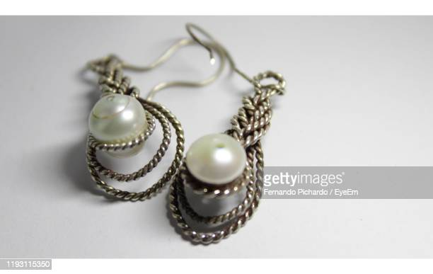 high angle view of earrings on white background - earring stock pictures, royalty-free photos & images