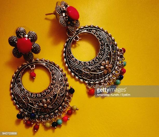high angle view of earrings on yellow background - イヤリング ストックフォトと画像