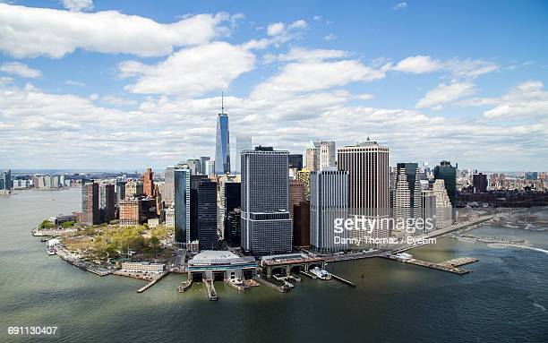 high angle view of east river by modern buildings against cloudy sky - lower manhattan stock pictures, royalty-free photos & images