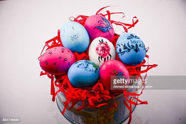 High Angle View Of Easter Eggs In Container Against White Background