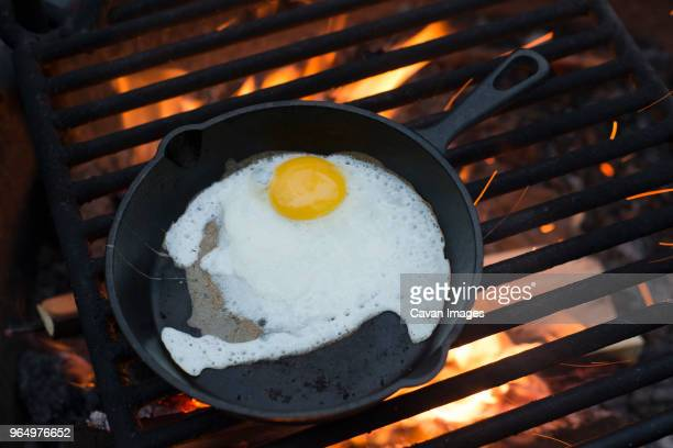 high angle view of egg in cast iron skillet on barbecue grill - ferro fundido - fotografias e filmes do acervo