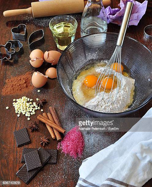 high angle view of egg yolk in bowl with ingredients on table - nathalie pellenkoft stock pictures, royalty-free photos & images