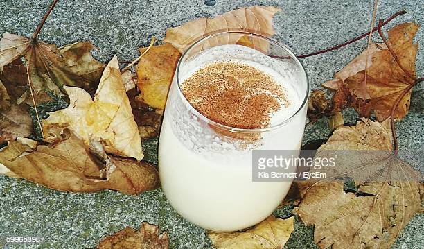 high angle view of eggnog in glass by leaves outdoors - eggnog stock photos and pictures